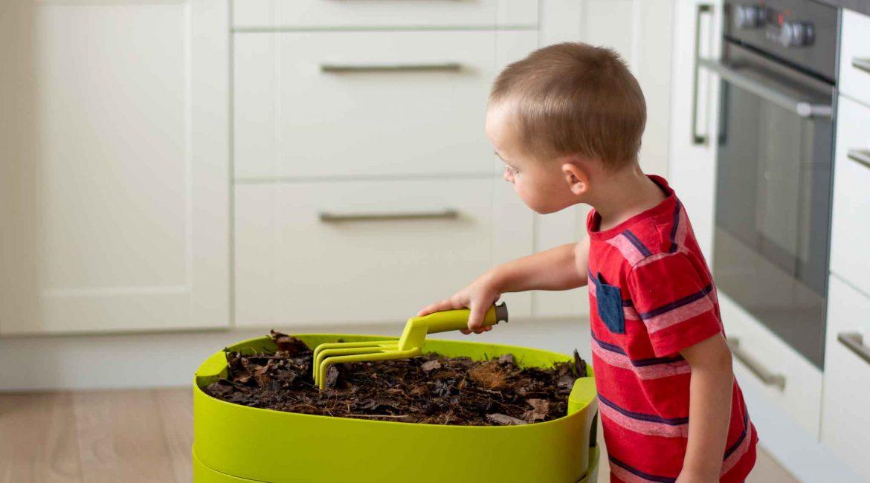 bytovy kompostér a dieťa, ktoré v ňom hľadá dážďovky